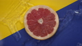 water flowing slow mo around grapefruit slice on yellow blue backdrop 77035316
