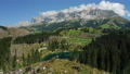 Women on top of hill with uprooted pine trees after strong wind in Lake Carezza - most beautiful lakes in South Tyrol, Dolomites. Circle drone motion 77050502