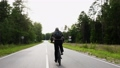 Guy with backpack rides cross-country mountain bike fast on an asphalt road through the green forest. View of the cyclist's back. Sport, recreation and pastimes, health benefits, fitness. Trip journey 77053206