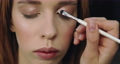 Closeup of perfect nude make-up process for young female model 77058233