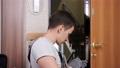 Skilled worker in uniform fixes front door lock in flat room 77062181
