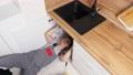 Employee unscrews details repairing waste trap under sink 77064067