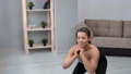 Smiling young sportswoman performing squats enjoying physical activity at cozy living room 77071184