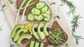 Sandwich with avocado, cucumber, olives and green onions on a wooden board. 77085620