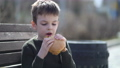 Hungry kid eating burger outdoor 77100048