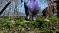 A volunteer man collects trash in a plastic bag in a city park 77102533
