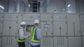 Engineers are walking to inspect electrical equipment in the factory. 77106287