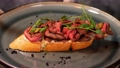 Baguette with beef slices decorated with micro-greenery are laid out in a plate with a beautiful decor. Slow motion. Restaurant dish. 77110000