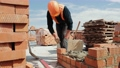 Close up of a man building a brick house. Laying red bricks on a construction site on a sunny day. House construction close up. 77112365