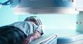 Elderly patient during futuristic MRI procedure 77113202