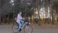 Young woman riding bicycle in autumn city park at sunset - slow motion 77113215