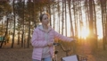 Slow motion: young woman walking with bicycle in autumn city park 77113222