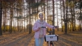 Slow motion: young woman walking with bicycle in autumn city park - front view 77113224