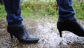 雨の中を歩く女性の足元 77116642