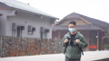 Young backpacker man is traveling alone and walking, looking around at an old train station in Taiwan with wearing mask. 77124225