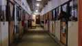 Equestrian - a man is cleaning in stalls and a woman brings equipment for horses 77135842
