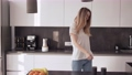 A young woman is dancing in the kitchen and drinking coffee 77161886