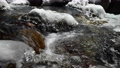 Close-up of a backwater of a mountain river flowing in a coniferous forest. Frozen stones in snow and ice. lateral movement sliding. Wide angle 77163598
