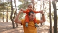 father and son in the park. happy family piggyback a kid dream concept. father holds baby son keeps on the neck in a forest park close-up. baby and parent man happy fun family walking in nature 77168193
