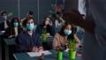 Masked multi-ethnic students studying chemistry 77169072