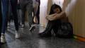 Upset asian schoolgirl sitting on floor at school 77169077