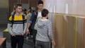 Bullies scoffing boy standing by school locker 77170266