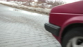 A red car stops on the road. Wheel stops spinning. Cobblestone road, winter day 77172622