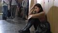 Sad asian girl sitting on floor by school locker 77175888