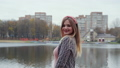 Girl posing in the autumn evening against the backdrop of a city lake. 77177158