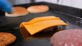 Hand putting processed cheese for burger to meat cutlet roasting on grill 77190548