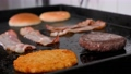Slices of bacon with meat patty for a burger fries on the grill. 77190555