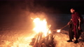 Viking with a torch lights bonfire. Brutal male of dangerous appearance fire. 77204244