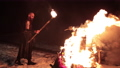 Viking with a torch lights bonfire. Brutal male warrior of dangerous appearance by the fire. 77204246
