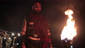 Viking with a torch lights bonfire. Brutal male warrior of dangerous appearance by the fire. 77204247