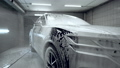 Close up, car washing process. Foaming detergent covers machine, cleans it from dirt. Slow motion, Detailing. 77211118