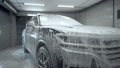 Close up, car washing process. Foaming detergent covers machine, cleans it from dirt. Slow motion, Detailing. 77211119