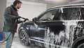 A Caucasian man works in a car wash. A car wash worker washes the car. The service employee washes the foam from the machine with a strong water pressure. 77211187