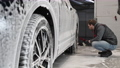 Car service: The worker washes car rims with a soft brush with shampoo 77211189