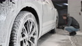 The employee works in the car wash. Washing the wheels with foam and water 77211190