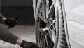 Hands of young man holding special cleaning brush, washing car wheel with foam. Cleaning of modern rims of luxury car at self car wash service. 77211193