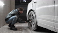 Car service: The worker washes car rims with a soft brush with shampoo 77211194