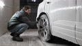 Foam drops from a modern SUV during car wash. Man using brush for cleaning the surface of the wheel rim of a car at auto wash 77211195