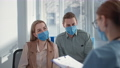 man and woman wearing protective masks on their faces because of dangerous virus, talking to female therapist during consultation with doctor in clinic 77231292