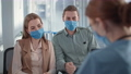 married couple wearing medical masks receive negative news during doctor consultation in hospital office 77231303