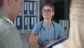 cheerful female doctor in medical clothes and glasses during consultation with married couple in hospital office, smiling and looking into camera 77231312