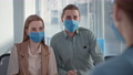 loving married couple wearing medical masks on their face while receiving patients in doctors office, smiling and looking into camera 77232985