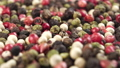 Shake a heap of assortment of bright multicolored peppercorns. Colored grains of spicy pepper seasoning. Macro. Slow motion 77243835