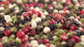 A mixture of different varieties of peppercorns. Colored seeds of assortment pepper. Rotation. Macro shot. Multicolored spicy condiments 77243836