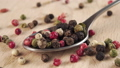 Grains of colored assorted dried spicy peppers fall into a spoon on a wooden background in slow motion. Macro shot. Multicolored peppercorn 77243838
