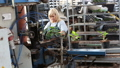 worker working with flowers in pots at industry conveyor 77255858